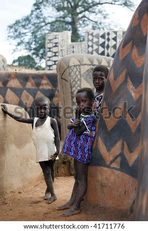 BURKINA FASO - AUG 10: gourounsi children are watching us on the visit of the village,are built with high walls to protect themselves from rival  attacks, August 10, 2009 at Tiebele, Burkina Faso - stock photo