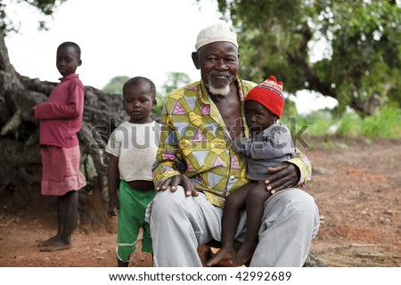 BURKINA FASO - AUGUST 12: Elder Lobi with baby, the elders have an important role making decisions on community standards, August 12, 2009 in Gaoua, Burkina Faso - stock photo