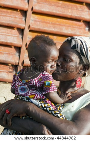 BURKINA FASO - AUGUST 9: mother kissing her daughter, women of ethnic Bissa lovingly of his children, August 9, 2009 in Country Bissa, Burkina Faso - stock photo