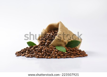 burlap bag with fair trade coffee, decorated with green leaves - stock photo