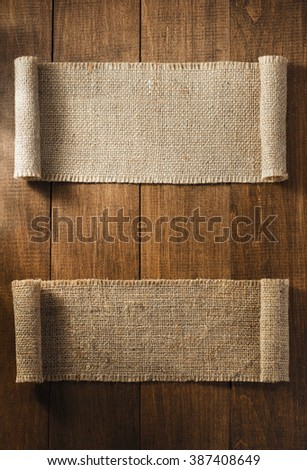 burlap hessian sacking on wooden background - stock photo