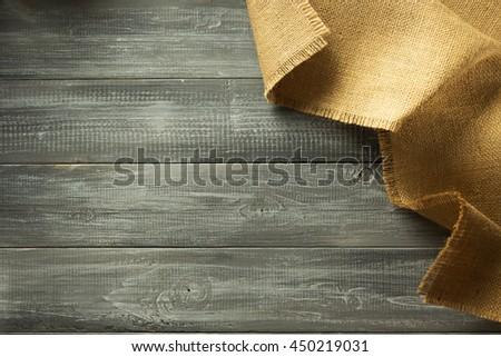 burlap hessian sacking on wooden background - stock photo