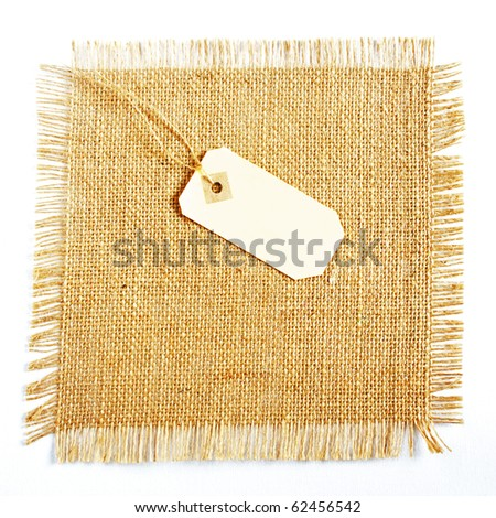 Burlap hessian square with gift tag isolated on white background - stock photo