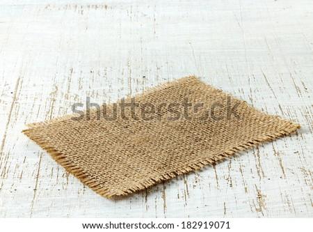 burlap napkin on old wooden table - stock photo