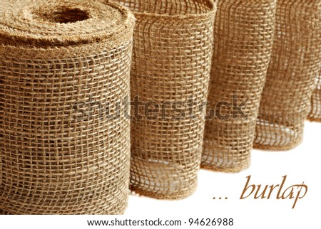 Burlap ribbon or garland (used for home decor and craft projects) on white background with copy space.  Macro with shallow dof.   Roughness concept  - could  be used to symbolize 'rough toilet paper'. - stock photo