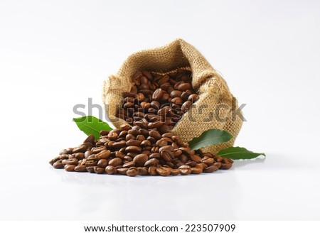 burlap sachet with roasted fair trade coffee, decorated with green leaves - stock photo