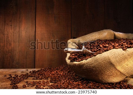 Burlap sack of coffee beans against dark wood background - stock photo