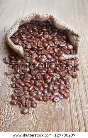 burlap sack of coffee beans on old wooden table - stock photo