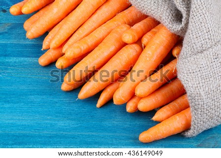 Burlap sack of freshly dug new carrots on a Wooden Table - stock photo
