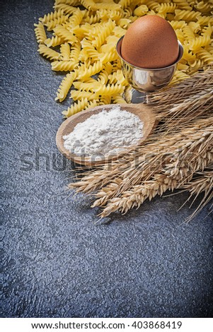 Burlap sack uncooked pasta wheat rye ears wooden spoon flour eggcup boiled egg on black background. - stock photo