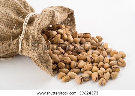 Burlap sack with pistachios salt spilling out over a white background - stock photo
