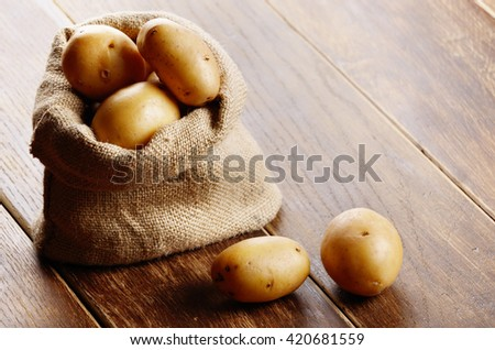 Burlap sack with potatoes on the wooden table - stock photo