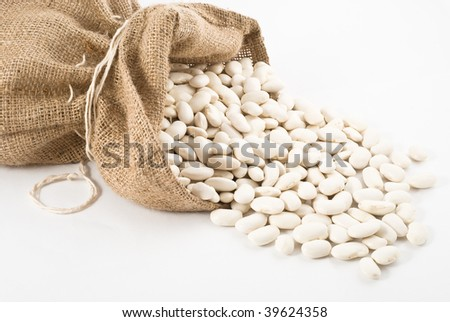 Burlap sack with white beans spilling out over a white background - stock photo