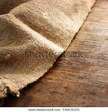 Burlap textile on wooden background - stock photo