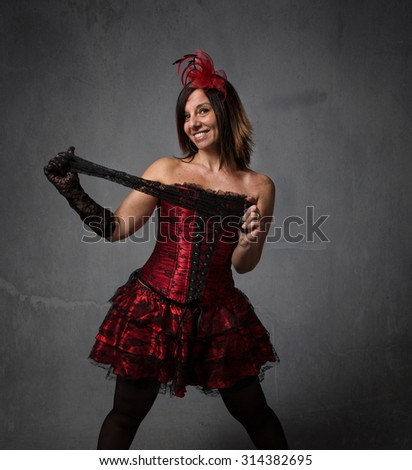 burlesque dancer playing with sock, dark background - stock photo