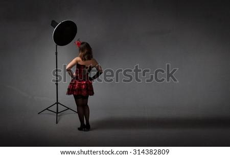 burlesque model in a photo shooting concept, dark background - stock photo