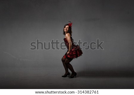 burlesque performing in dark room, red dress - stock photo