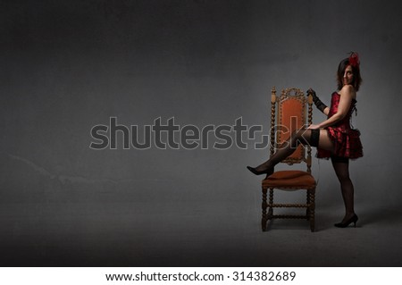burlesque woman play with chair, dark background - stock photo