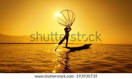 Burma Myanmar Inle lake fisherman on boat catching fish by traditional net. Outdoor sunset photography - stock photo