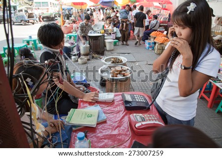 BURMA, RANGOON - FEBRUARY 13, 2011: People are making calls in local phone booth on street market. - stock photo