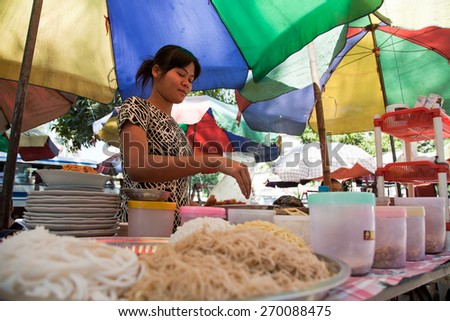 BURMA, RANGOON - FEBRUARY 12, 2011: Street local restaurant with woman preparing noodle food. - stock photo