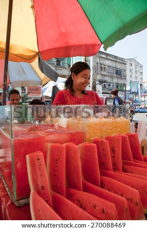 BURMA, RANGOON - FEBRUARY 12, 2011: Woman is selling on street market slices of fresh watermelon. - stock photo