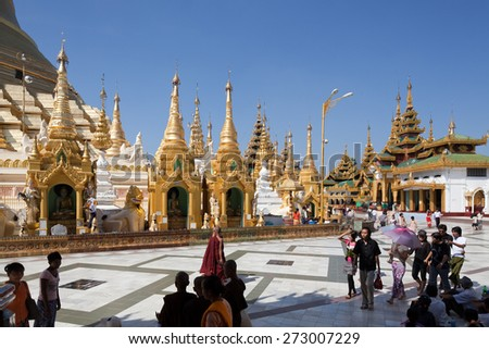 BURMA, RANGOON, SHWEDAGON PAGODA - FEBRUARY 11, 2011: Walking people in the biggest Buddhist temple Shwedagon pagoda. - stock photo