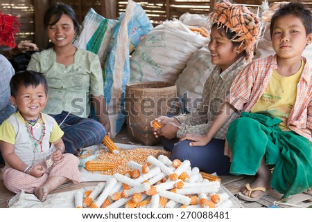 BURMA, SHAN STATE, SAMKAR -  FEBRUARY 25, 2011: Pa-O tribal woman and kids in native costume are sitting around corn harvest. - stock photo