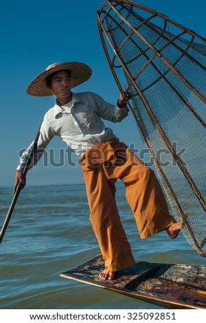 Burmese fisherman on bamboo boat catching fish in traditional way with handmade net. Inle lake, Myanmar (Burma) travel  destination - stock photo