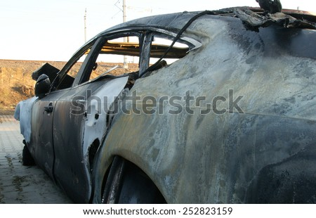 Burn sports car wreck - left side - stock photo