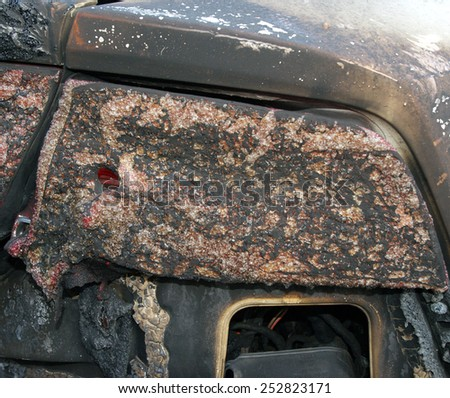 Burn sports car wreck - right rear light (focus on only part of the image intentionally) - stock photo