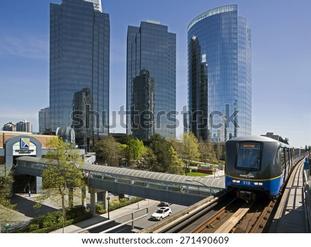 BURNABY - APRIL 19, 2015: Town centre Metropolis at Metrotown with 400 stores and services is British Columbia's largest shopping centre. Three towers, SkyTrain station and bridge in this picture. - stock photo