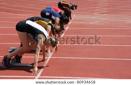 BURNABY, CANADA - JULY 9: unidentified girls on the start of the 100 meters dash on the 24th Annual Trevor Craven Memorial Track & Field Meet on July 9, 2011 - Swangard Stadium, Burnaby, Canada - stock photo