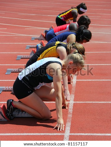 BURNABY, CANADA - JULY 9: unidentified girls on the start of the 100 meters dash on the 24th Annual Trevor Craven Memorial Track & Field Meet on July 9, 2011 - Swangard Stadium, Burnaby, Canada