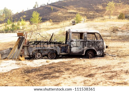 Burned car on desert rural road after forest fire - stock photo