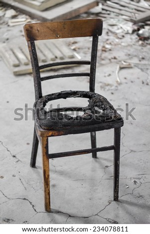 Burned chair in an old building - stock photo