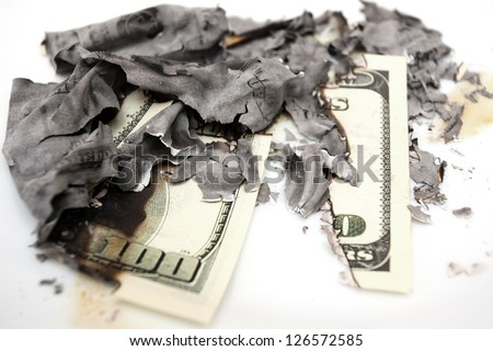 burned dollar bills on white background - stock photo