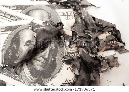 burned dollar bills on white background  - stock photo