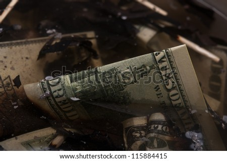 burned dollars in a scrapyard - stock photo