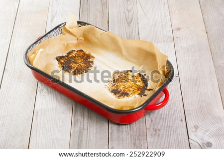 burned food prints on baking paper, old enamel frying pan on wooden table - stock photo