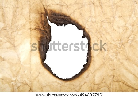 Burned hole on a vintage paper background