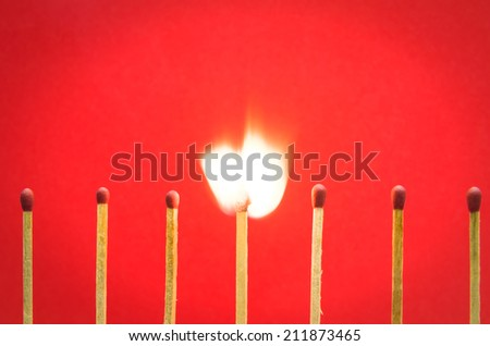 burned match setting on red background for ideas and inspiration - stock photo