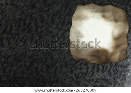 Burned paper put on the black color leather background represent the retro style and vintage paper concept related idea. - stock photo