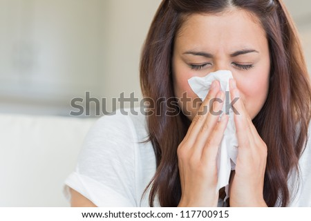 Burnette woman blowing nose into tissue - stock photo
