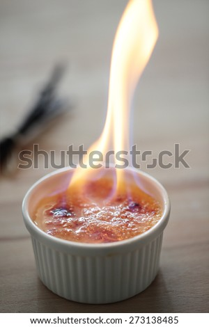 Burning alcohol on the top of creme brulee dessert - stock photo