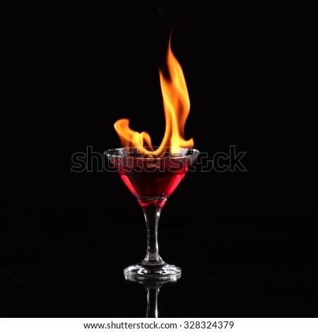 Burning alcoholic drinks with ice cubes, on black background - stock photo