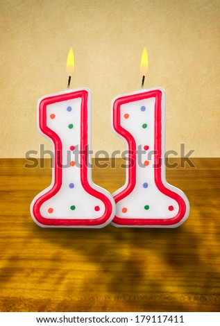 Burning birthday candles number 11 - stock photo