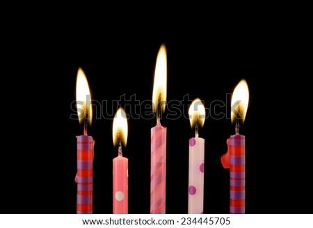 Burning birthday candles on black background  - stock photo