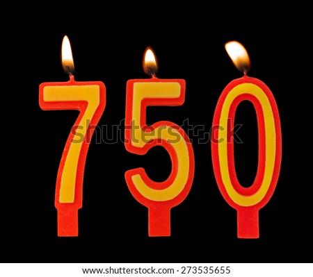 Burning birthday candles on black, number 750 - stock photo