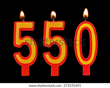 Burning birthday candles on black, number 550 - stock photo